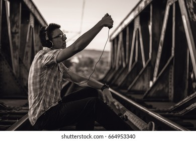 Young man with headset and mobile phone on bridge make selfie.