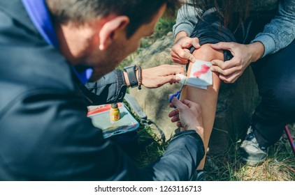Young man healing knee to a young woman who has been injured doing trekking