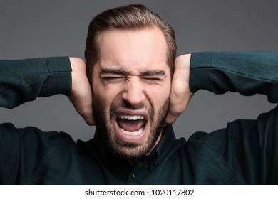Young man with hearing problem covering ears on grey background