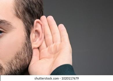Young man with hearing problem on grey background, closeup