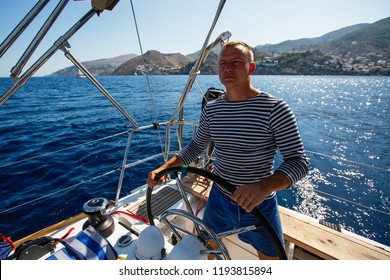 Young man at the helm of a sailing yacht boat.