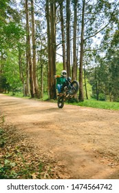 Young man with helmet doing wheelie with a custom motorbike outdoors
