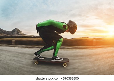 A young man in helmet and a leather suit in a special rack rides a longboard on afsaltu on background mountains and beautiful sky