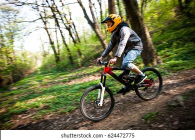 young man with helmet ride mountain bike through forest