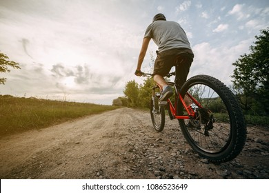 Young man in helmet riding a bicycle along country road on sunset sky background. Bicycle sports, traveling, healthy lifestyle and activity.