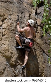 The young man in helmet rises on a rock