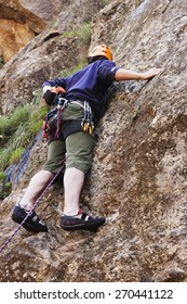 A young man with helmet and rope climbing safely a rock wall outdoors.