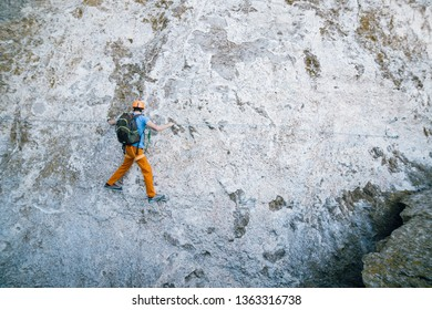 Young man in helmet and special equipment going along via ferrata in the mountains cave.