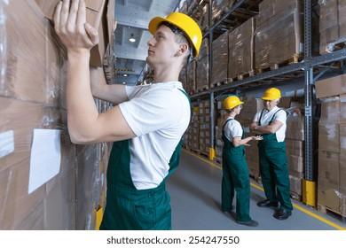 Young man in helmet working in big warehouse
