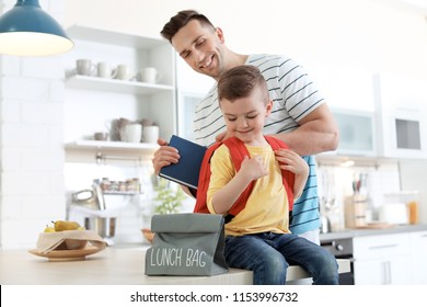 Young man helping his little child get ready for school at home