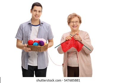 Young man helping a mature lady knit isolated on white background