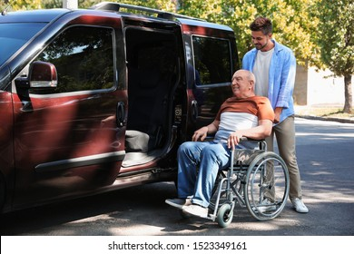 Young man helping patient in wheelchair to get into van outdoors
