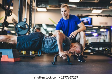 Young man helping senior man in a workout. Personal trainer job. Staying in shape.