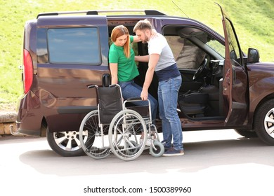 Young man helping woman to get out from van into wheelchair outdoors