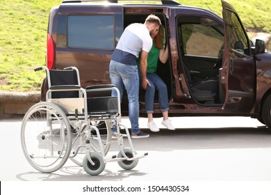 Young man helping woman to get out from van,  focus on wheelchair outdoors