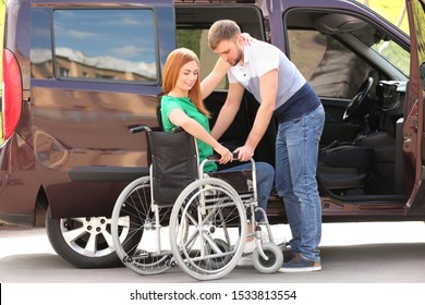 Young man helping woman to sit into wheelchair near van outdoors