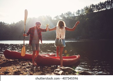 Young man helping woman to step into the kayak. Couple going for a canoe ride in the lake.