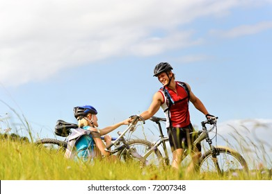 young man helps a fellow cyclist who has fallen over while mountain bicycle outdoors