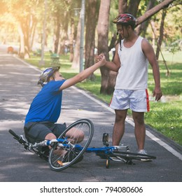 A young man helps his friend who get bicycle accident on a path.