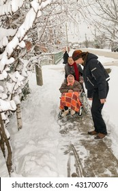 The young man helps to pull out an invalid carriage from a snowdrift. A family on walk.