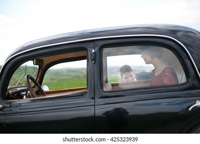 Young man hides from the lady in vintage car