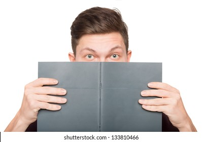 Young man hiding behind a book