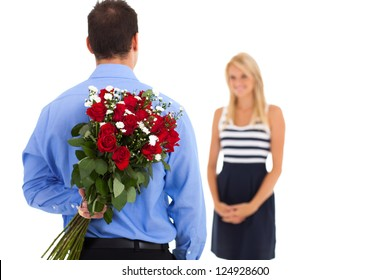 young man hiding bunch of roses behind his back to surprise his girlfriend on valentine's day