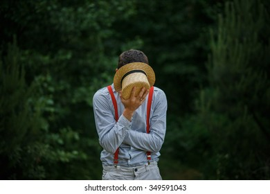 Young man hiding in a straw hat