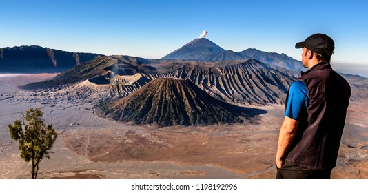 Young man hiker looking at smoking volcano Mt.Bromo. Scenic view point King Kong hill in Java. Popular place for photographers and tourists. Summer treking and hiking in Indonesia. Sand valley vantage