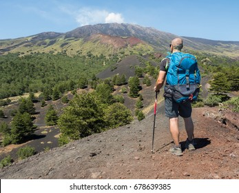 young man hiker looks the Etna's Valley While the volcano smokes. picture take from the back side while the guy dress his backpack holding pole walck