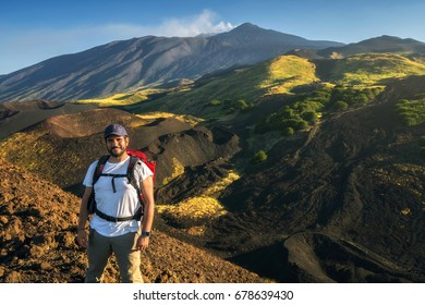 young man hiker looks the Etna's Valley near an old crater during a trekking day