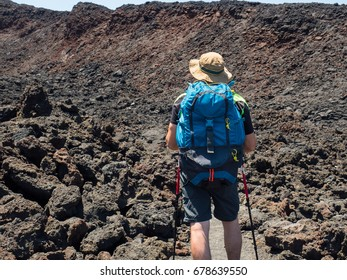 young man hiker making trekking on a old vulcano crater. picture take from the back side while the guy dress his backpack holding pole walck - Etna's valley land