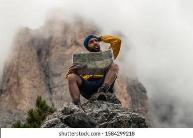 Junge Wanderer, die auf dem Steinberg sitzen, lesen Karte, mit bewölktem Himmel und Nebel. Gelbe Jacke, Rucksack, schwarzer Bart und Mütze. Reisedolomiten, Italien.