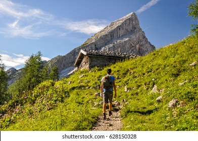 "Young man hiking on a pathway up to Watzmann Mountain (2713m). In the background you can see a cabin and  ""Kleiner Watzmann"" (Little Watzmann, 2307m). Sunny day in the Bavarian Alps in Germany."