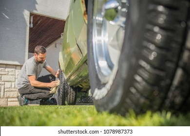 Young man with a hip beard cleaning a wheel of an old green vintage car on a home lawn. Cleaning muscle car tires at home with a cloth.