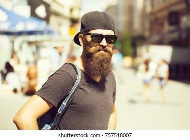 Young man hipster with beard and moustache on handsome face in casual dark shirt black sunglasses baseball cap and denim bag posing on city street background outdoor