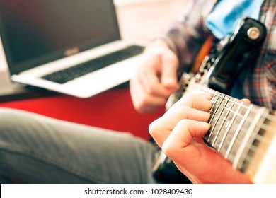 Young man, hipster folk singer songwriter in checkered plaid shirt, playing sunburst offset electric guitar. Male guitarist taking online jazz music courses on pc laptop computer. Background, close up
