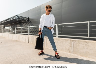 Young man hipster in stylish clothes in sunglasses with a black cloth bag in vintage sandals stands is in a city near a gray building. American guy. Fashionable men's summer clothes. Youth style.