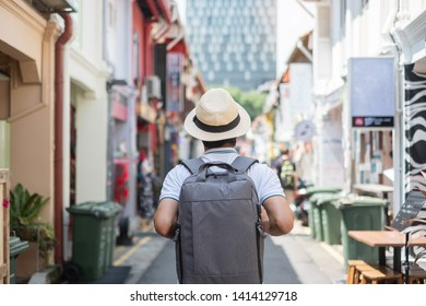 Young man hipster traveling with backpack and hat, happy Asian traveler walking at Haji Lane and Arab street in Singapore. landmark and popular for tourist attractions. Southeast Asia Travel concept