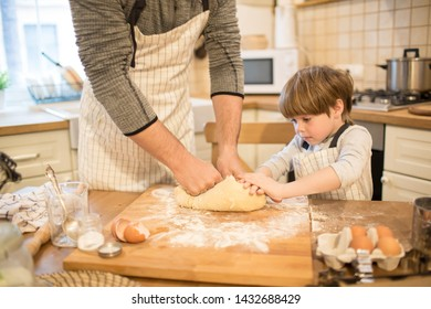 A young man and his child are preparing flavored cookies or pizza in a spacious white kitchen. Dad teaches his kid to cook. Joint pastime with family.