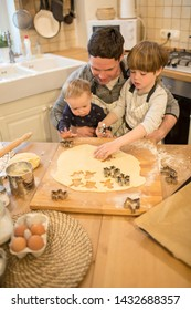 A young man and his children are preparing flavored cookies in a spacious white kitchen. Dad teaches his children to cook. Joint pastime with family.
