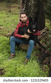 Young man with his dog in the forest, selective focus