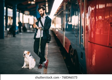Young man and his dog waiting train. Handsome man using mobile phone at the train station.
