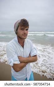 A young man in his early twenties stand by the ocean on the beach on a cool day with a beeny on his head and his arms folded.
