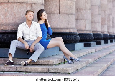 Young man and his girlfriend sit on base of the column in a relaxed poses and smile
