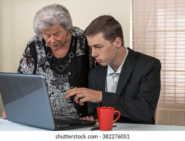 A young man and his grandma working together on laptop