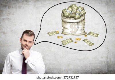 young man with his hand to the chin thinking about money. A picture of a bag of money to the right. Front view. Concrete background. Concept of having a lot of money.