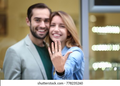 Young man and his happy fiancee showing engagement ring against blurred background