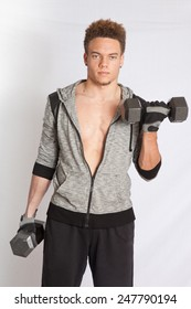 Young man with his jacket open, working out with dumb bells