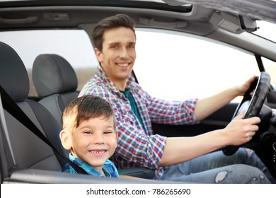 Young man and his little son in car